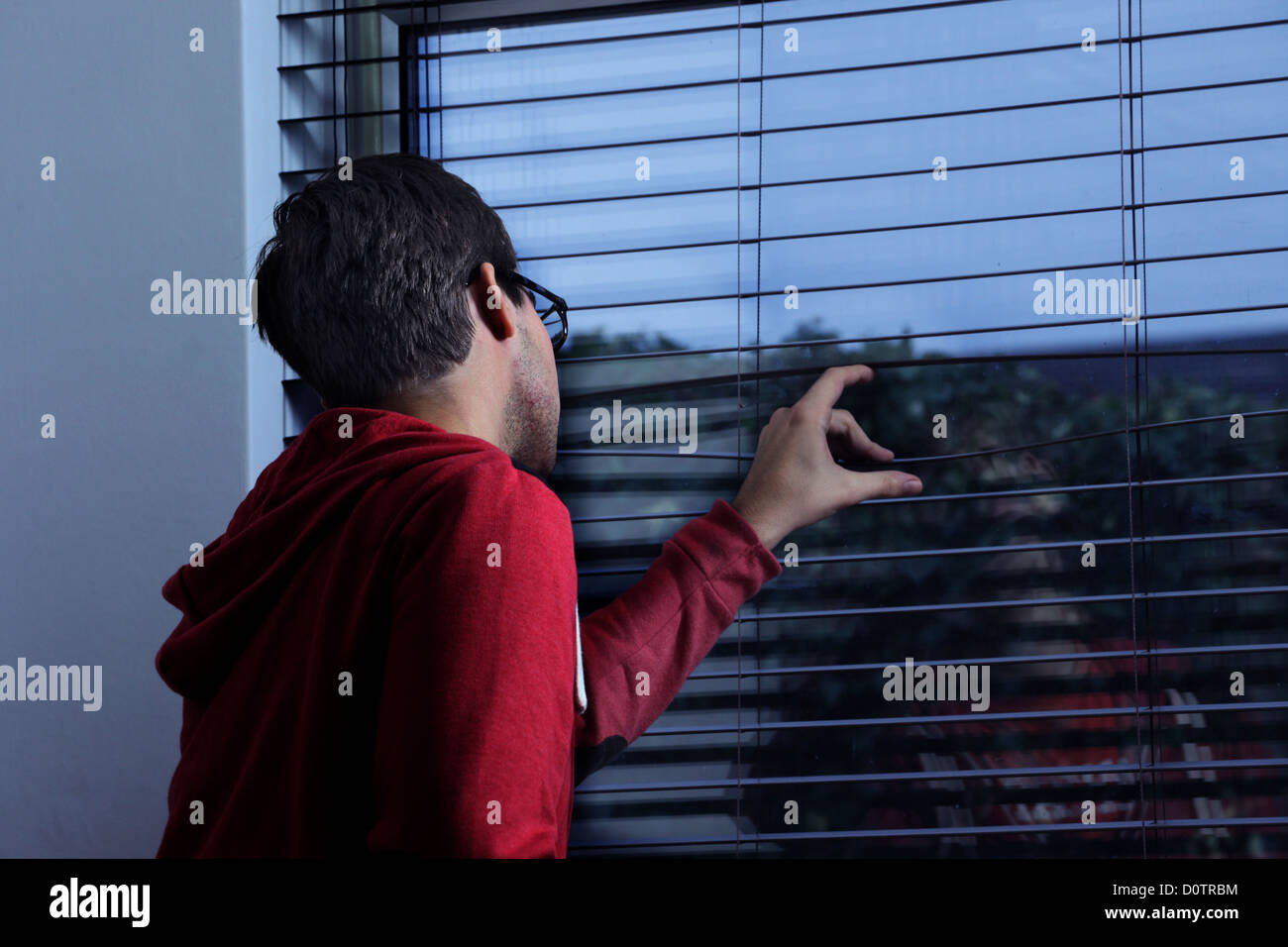 Young male wearing glasses looking out through a window blind at night. Back view. - Stock Image