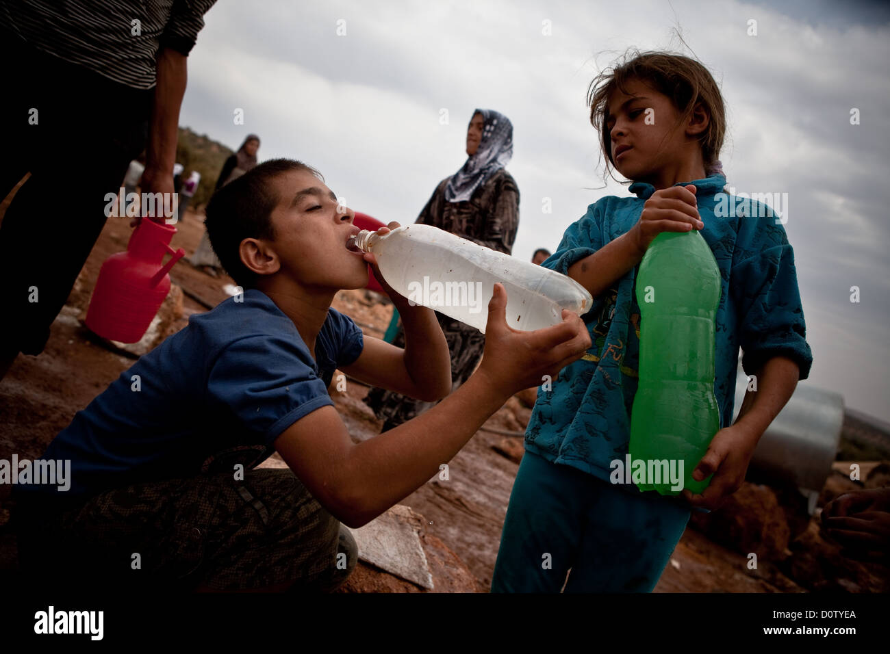 02/10/12, Atmah refugee camp, Atmah, Syria. Children tentatively sip the cloudy water supplied to them at the camp. - Stock Image
