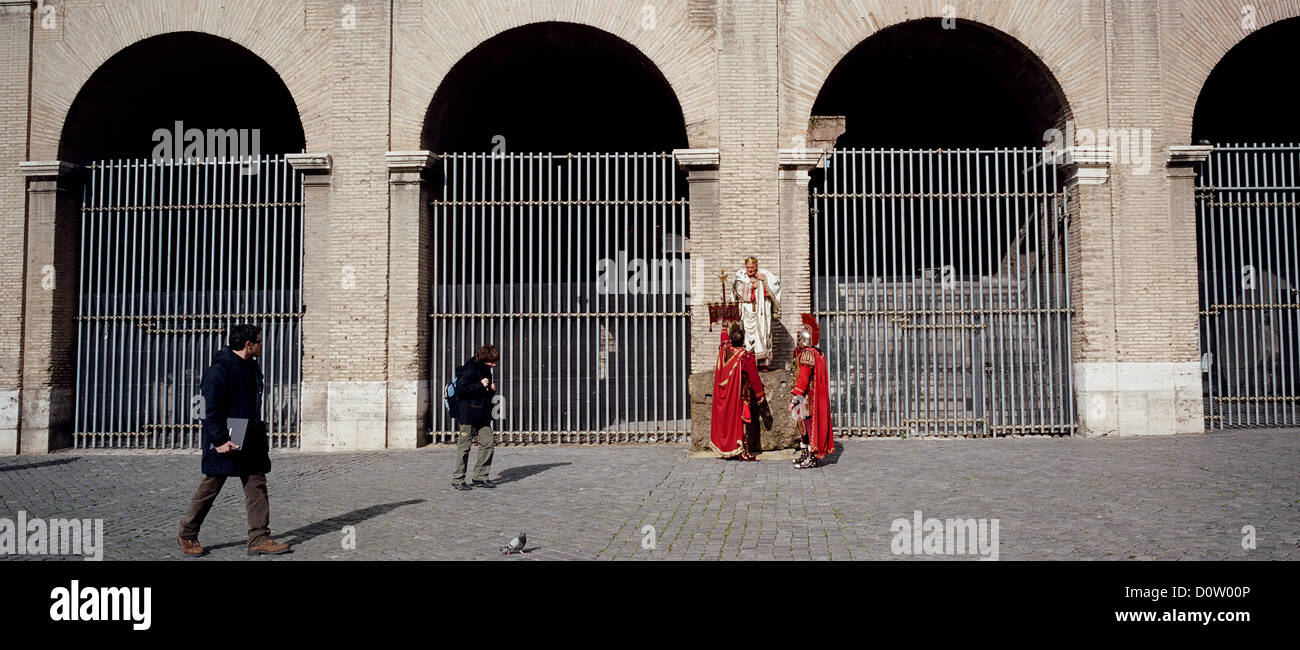 Men dressed in Roman costumes wait for tourists to pay for photographs with them outside the Colosseum in the center Stock Photo