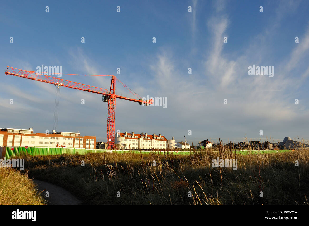 Large crane on a construction site against a dramatic blue sky with trailing clouds - Stock Image