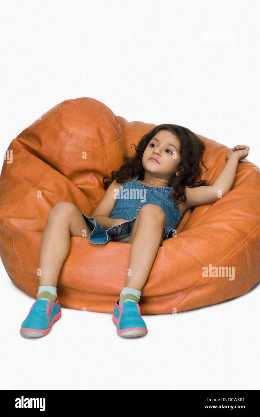 Girl relaxing on a bean bag - Stock Image