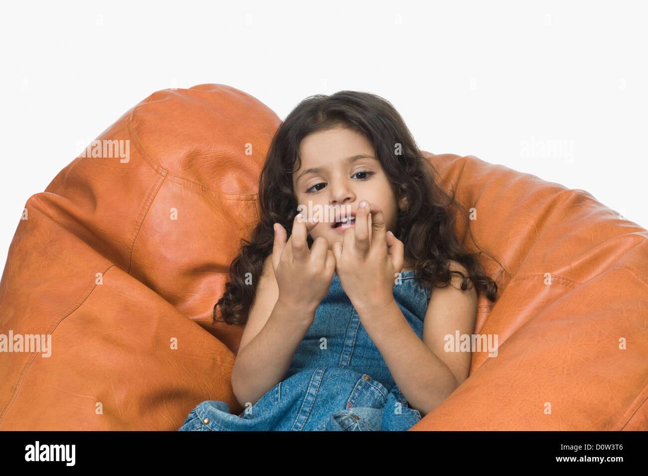 Girl playing on a bean bag - Stock Image