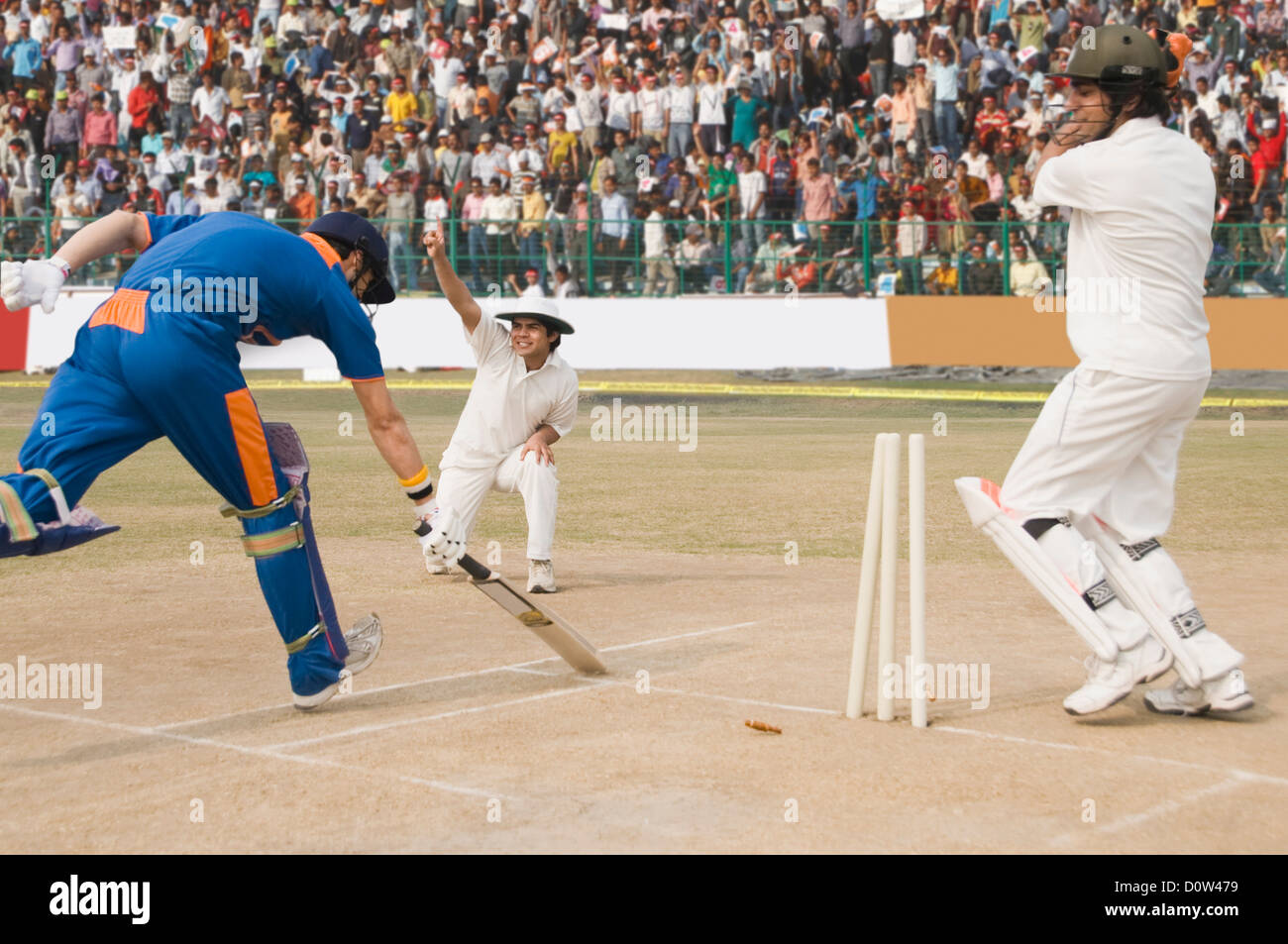 Cricket batsman scoring a run and fielder appealing for run out - Stock Image