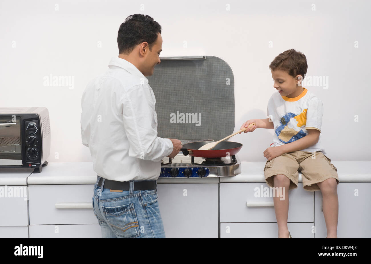 Man and his son preparing food in a kitchen - Stock Image