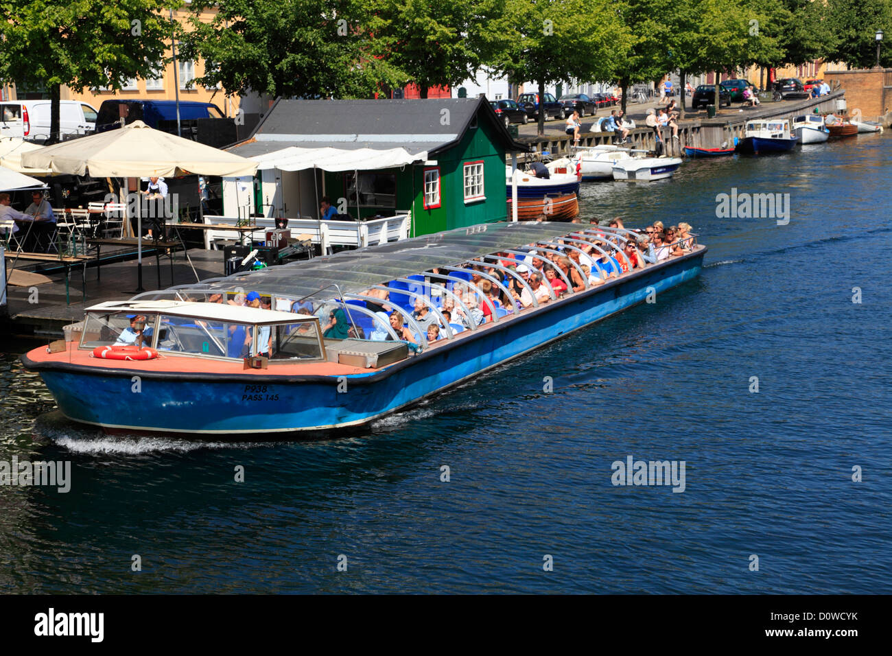 Canal cruise boat in the old and cosy Christianshavns Canal in Copenhagen, Denmark, with restaurants and cafés - Stock Image