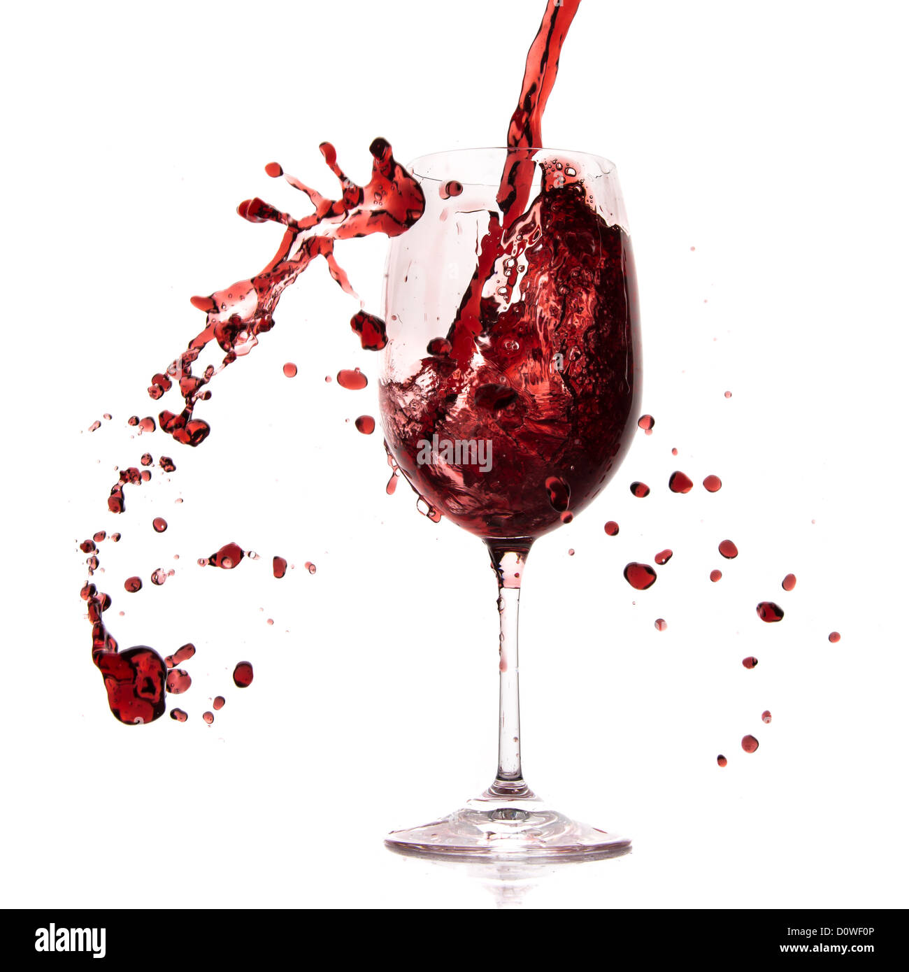 pouring red wine in goblet, isolated on white Stock Photo