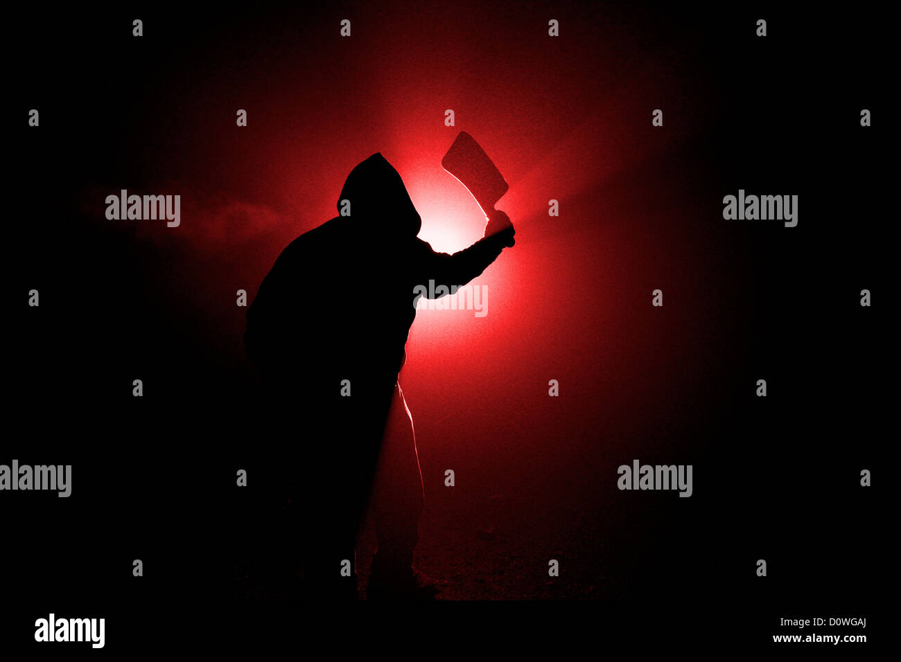 Cleaver Killer: Dark, foggy outdoor silhouette of a man wielding a large cleaver.  Duotone red. - Stock Image