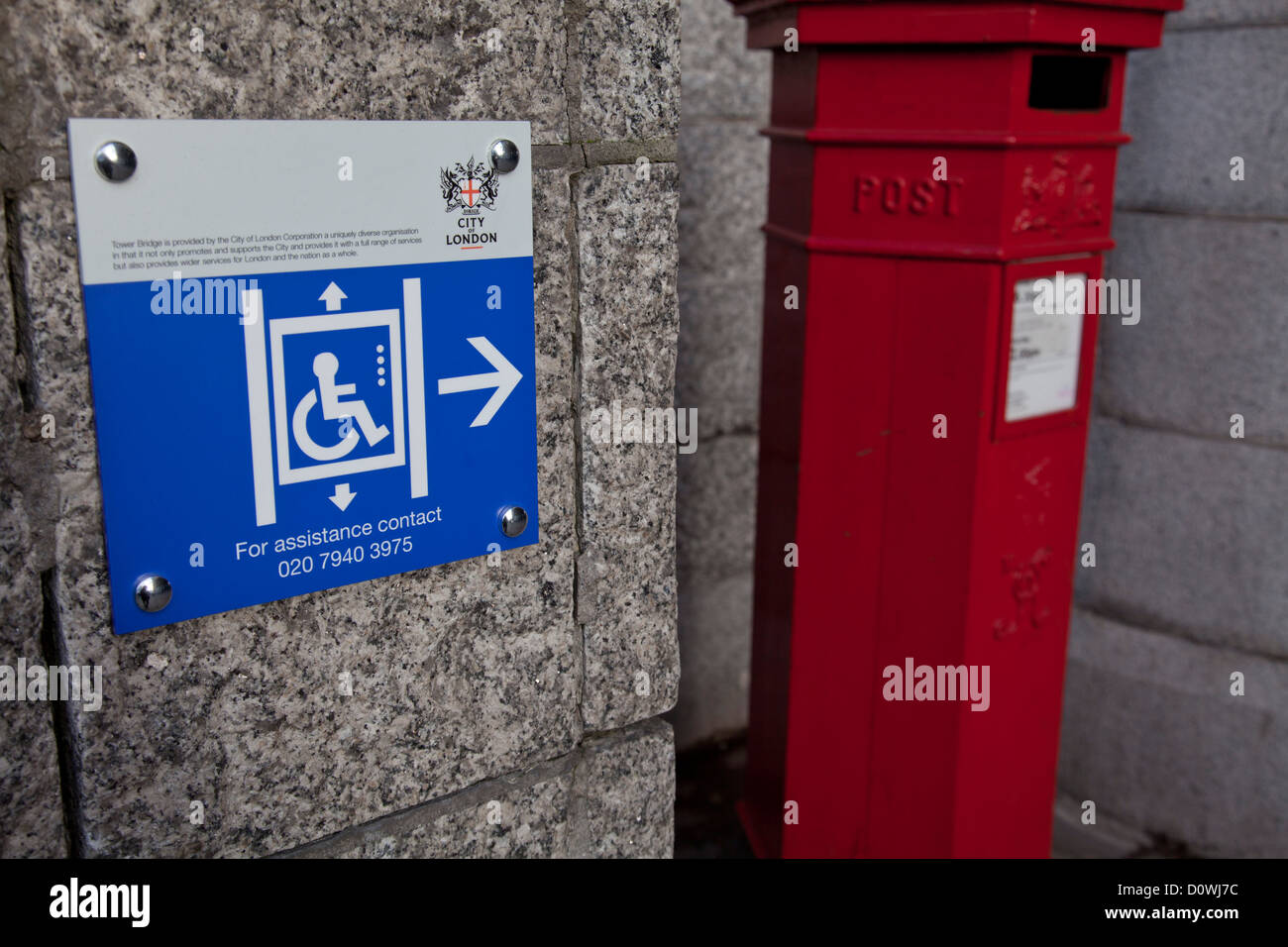 Wheelchair and disability access sign next to a postbox in London, England, UK - Stock Image