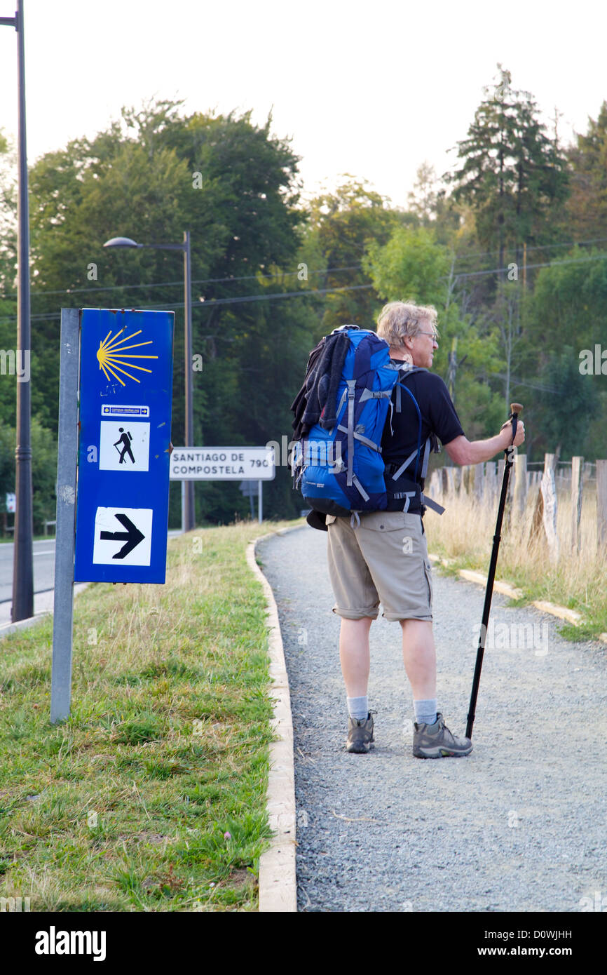Pilgrim standing beside the Camino sign, mileage marker on the side of the road, to Santiago de Compostela, Ronscevalles - Stock Image