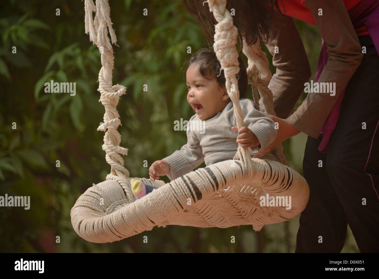 cute south asian (indian) baby girl playing on a swing stock photo