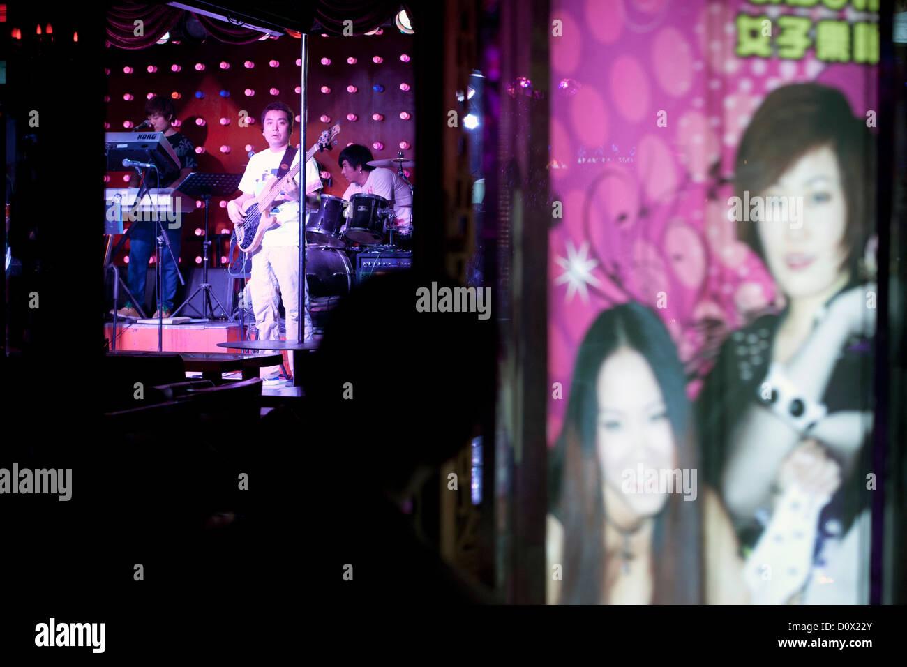 A musician playing guitar in a waterside bar on Shichahai Street (Lotus Market), Beijing, China. - Stock Image