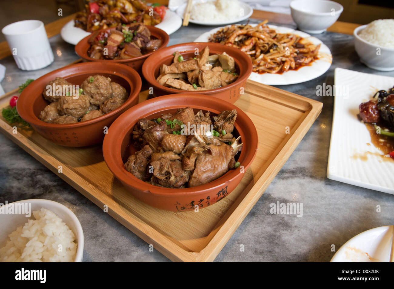 A traditional lunchtime meal served in a restaurant in Beijing China, consisting of duck and pork dishes with rice Stock Photo