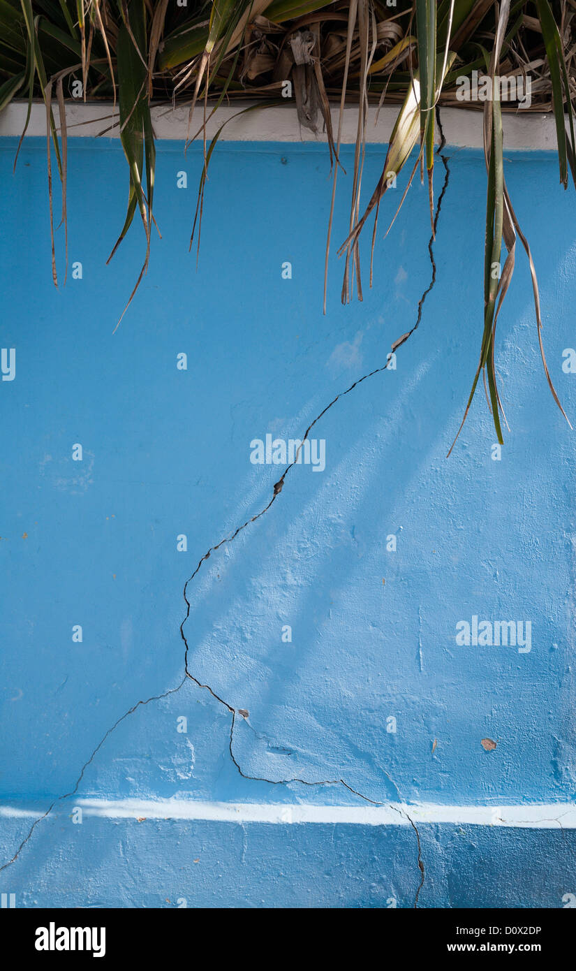Cracked Blue Wall. A crack in a painted blue concrete wall. Splits at the bottom. Hopetown, Abaco, Bahamas - Stock Image