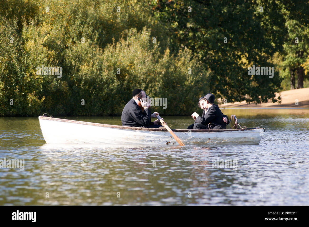 Orthodox Jewish man using a mobile phone in a rowing boat, Hollow Ponds, Leytonstone, London, England Stock Photo