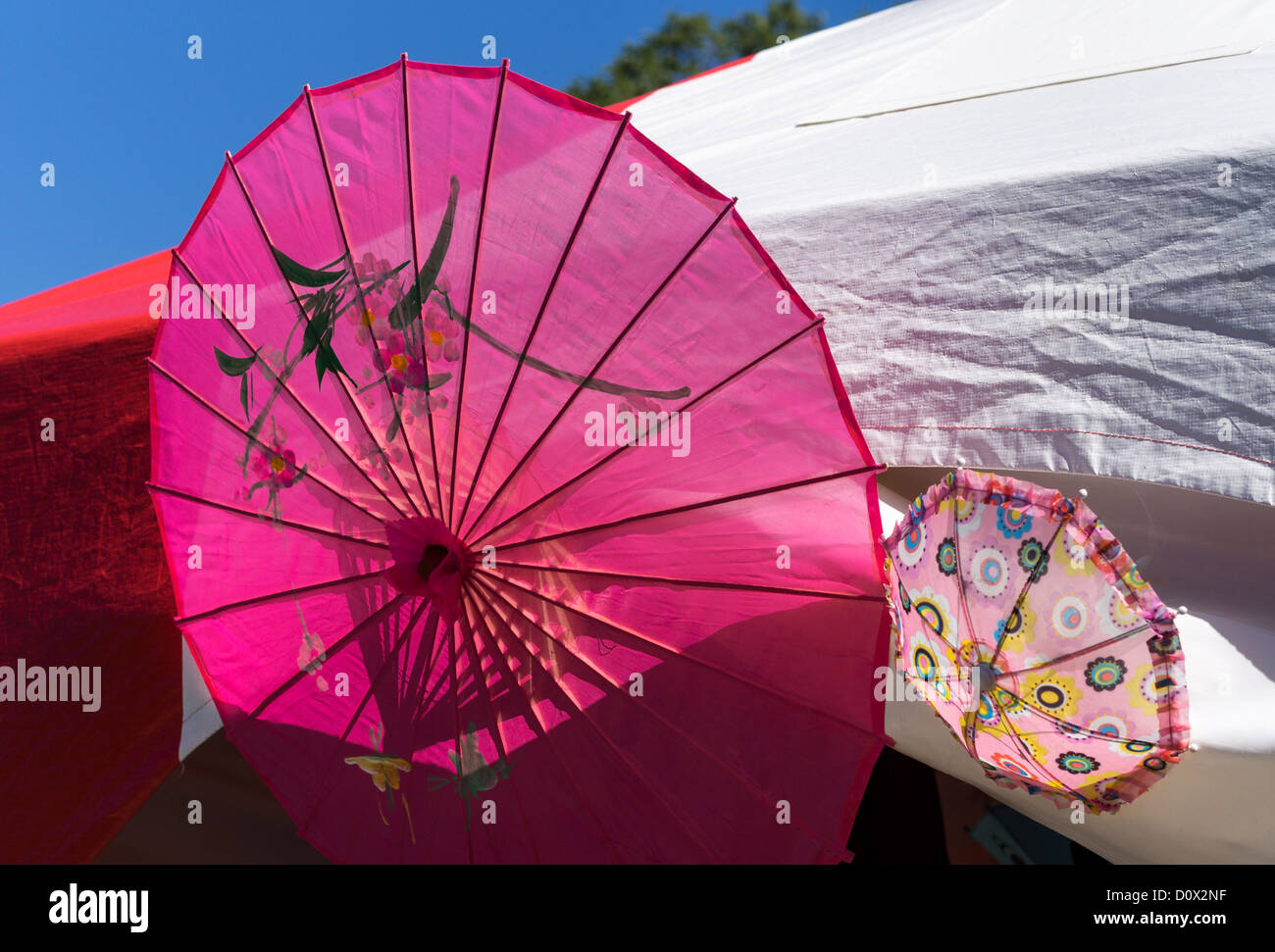 Parasol Decorations. Two brightly coloured parasols decorate a tent at Edmonton's Heritage Festival. - Stock Image