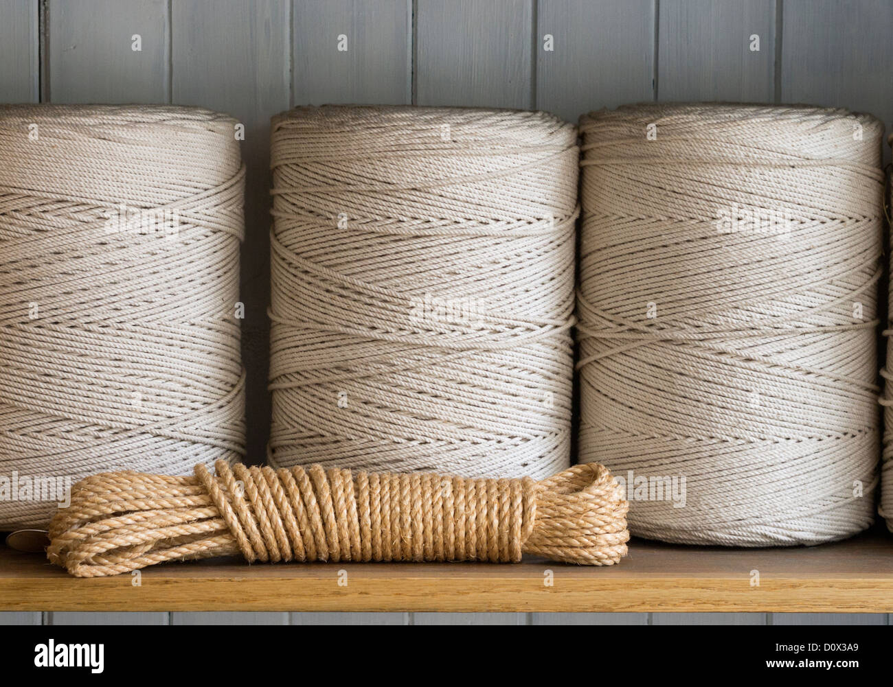 Three spools of cord and a bit of twine. A shelf of string. - Stock Image