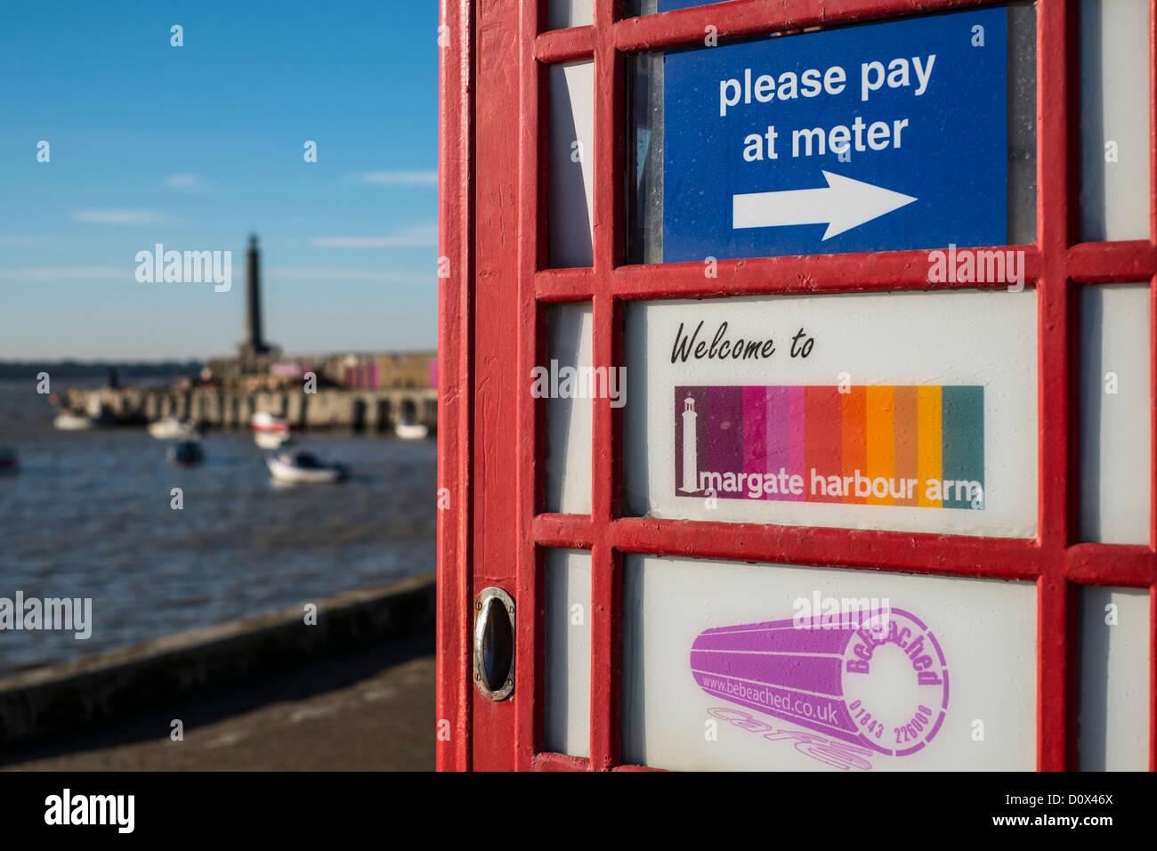 Red Public Telephone Kiosk Advertising 'The Harbour Arm' Margate, Kent, UK. - Stock Image