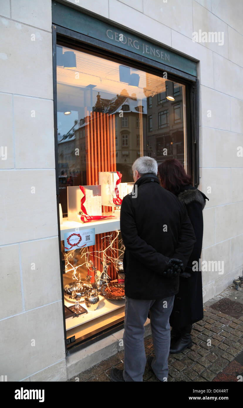 Couple looking at the Georg Jensen silversmith life style shop's Christmas display on pedestrian street Strøget, - Stock Image