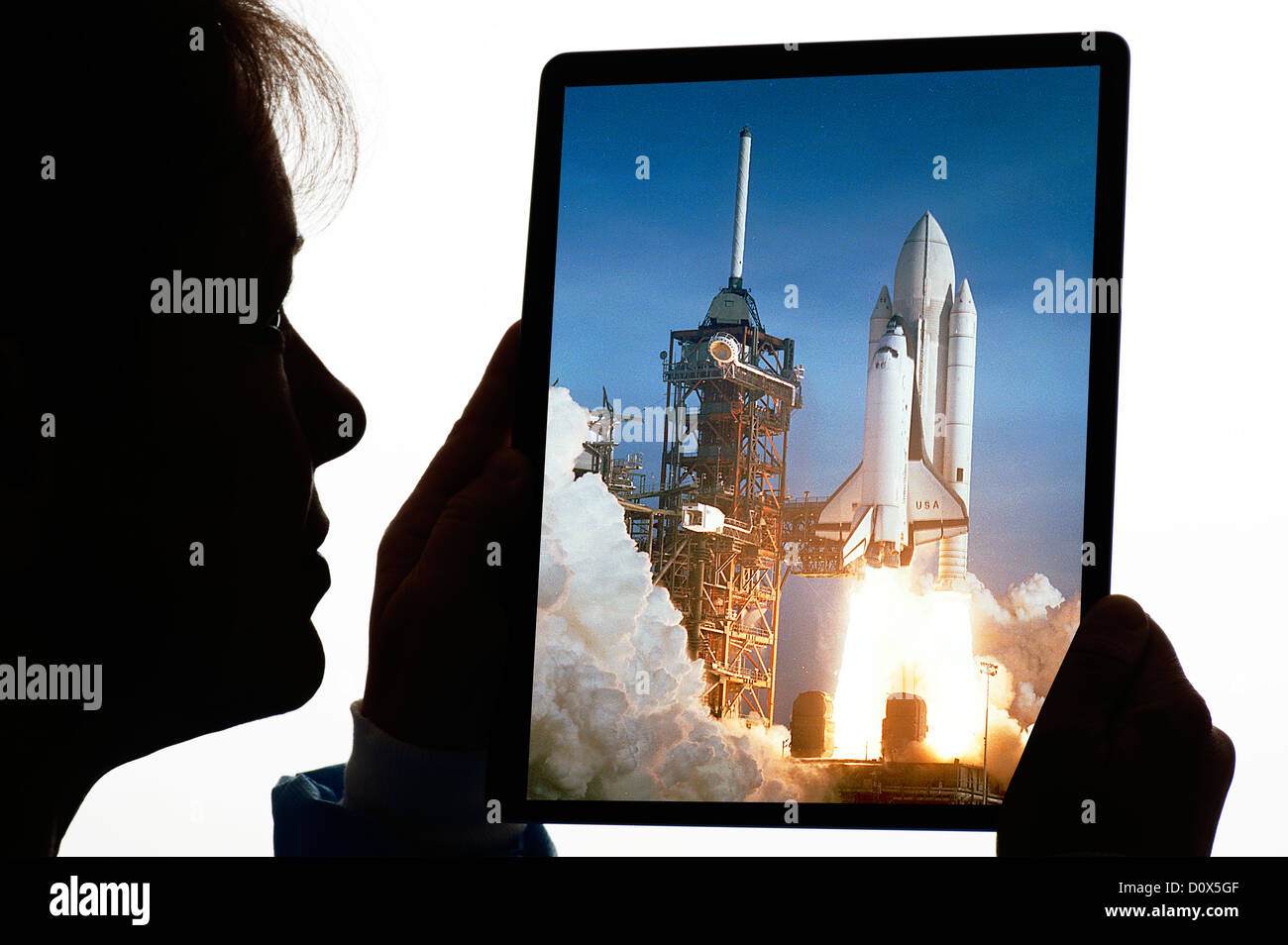 woman engineer with NASA shuttle launch photo on digital tablet - Stock Image