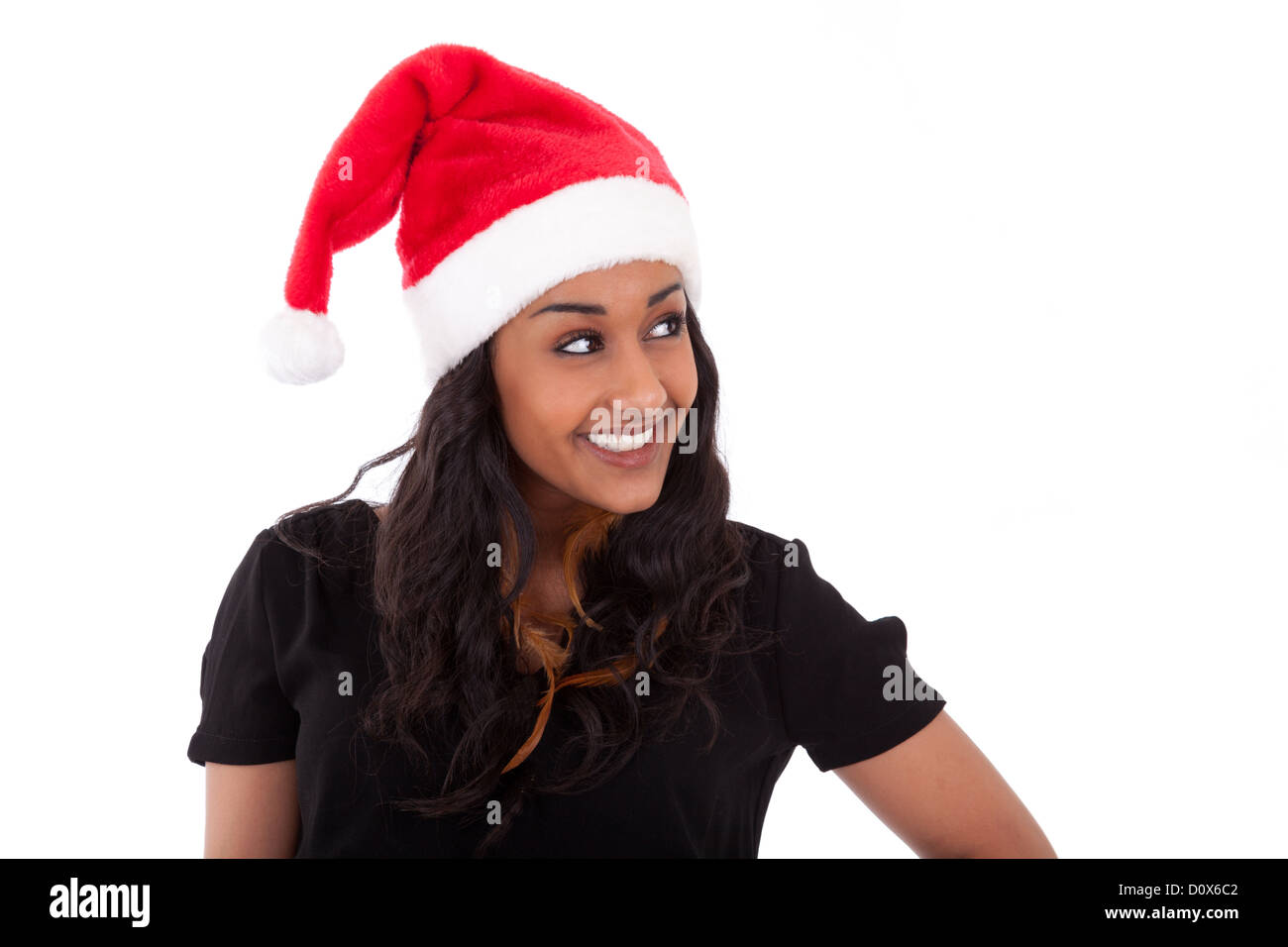 Young African American woman wearing a santa hat, isolated on white background - Stock Image