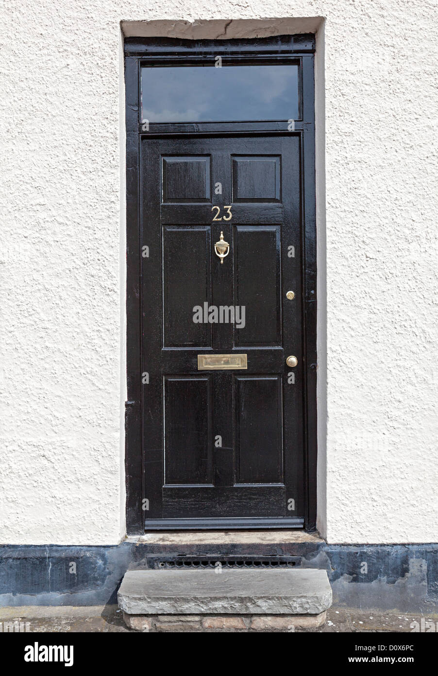Black house door with number 23 opening directly onto street, Wales, UK - Stock Image