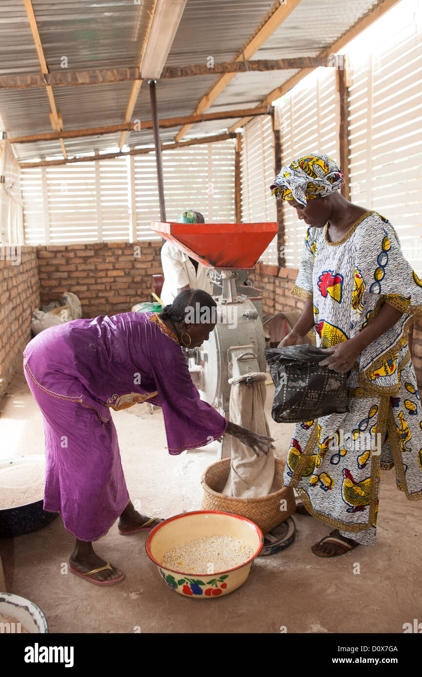 Women grind corn into flour at a mill in Doba, Chad, Africa. Stock Photo