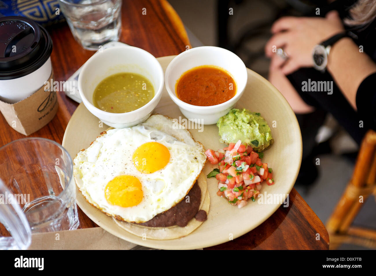 Mexican breakfast huevos rancheros. Eggs, salsa, guacamole,  Traditional Mexican breakfast at a restaurant. - Stock Image