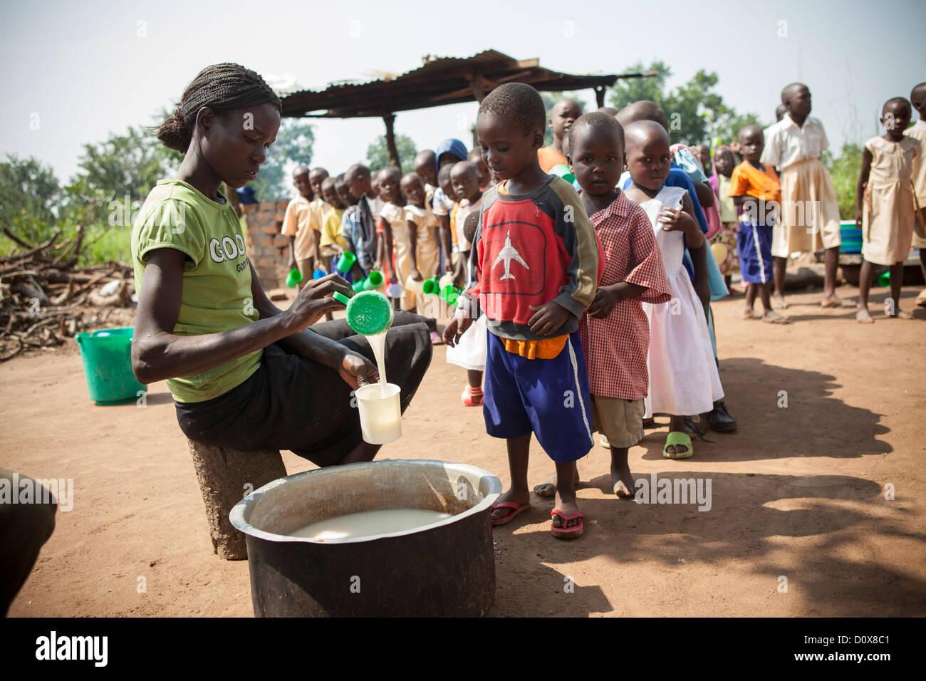 Students receive porridge at break time a school in Amuria, Uganda, East Africa. - Stock Image