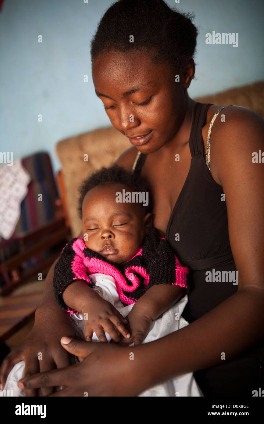 Teenage mother and her sleeping baby at their home in Kasese, Uganda. - Stock Image