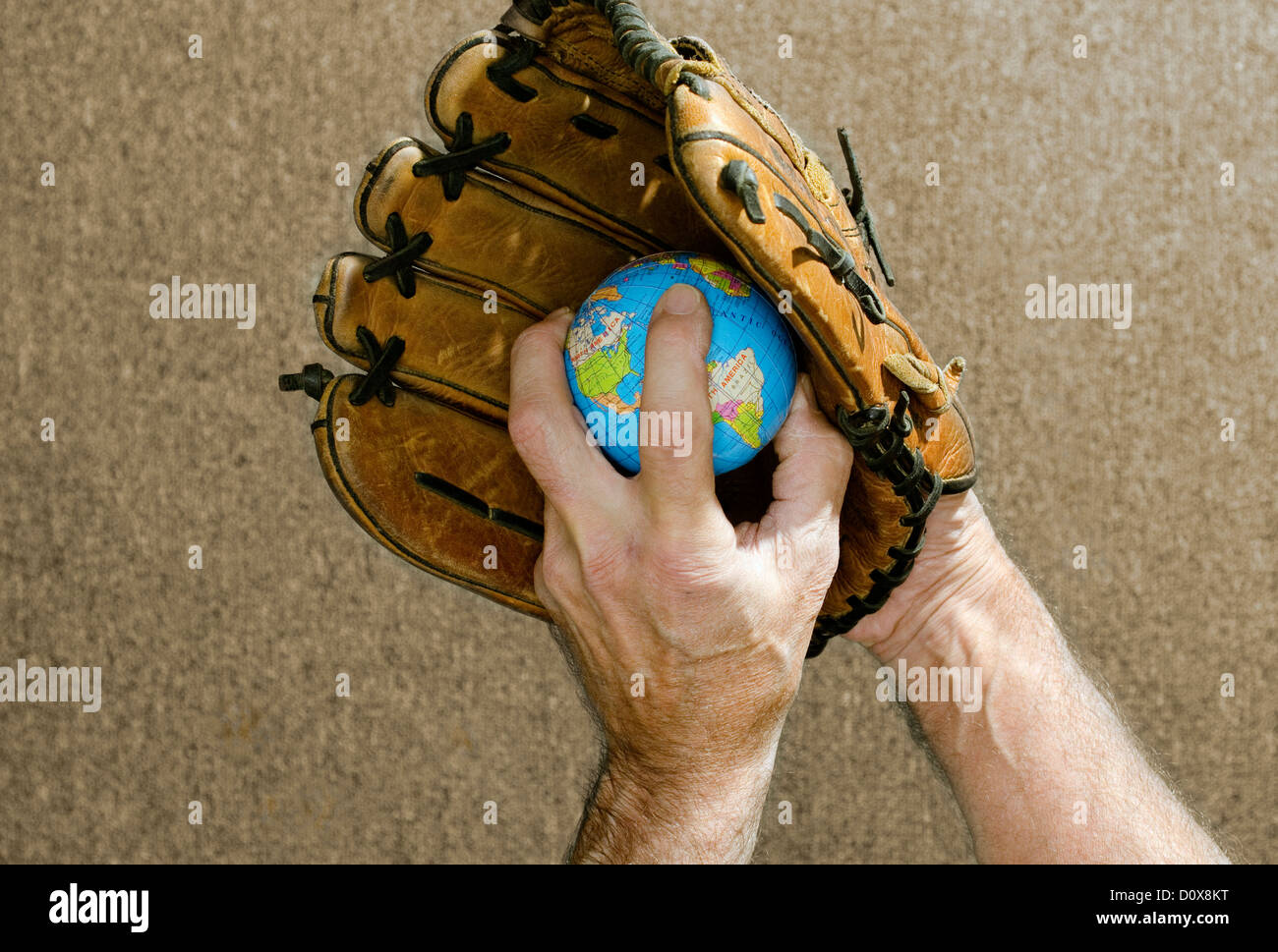 baseball pitcher holding globe in baseball glove - Stock Image