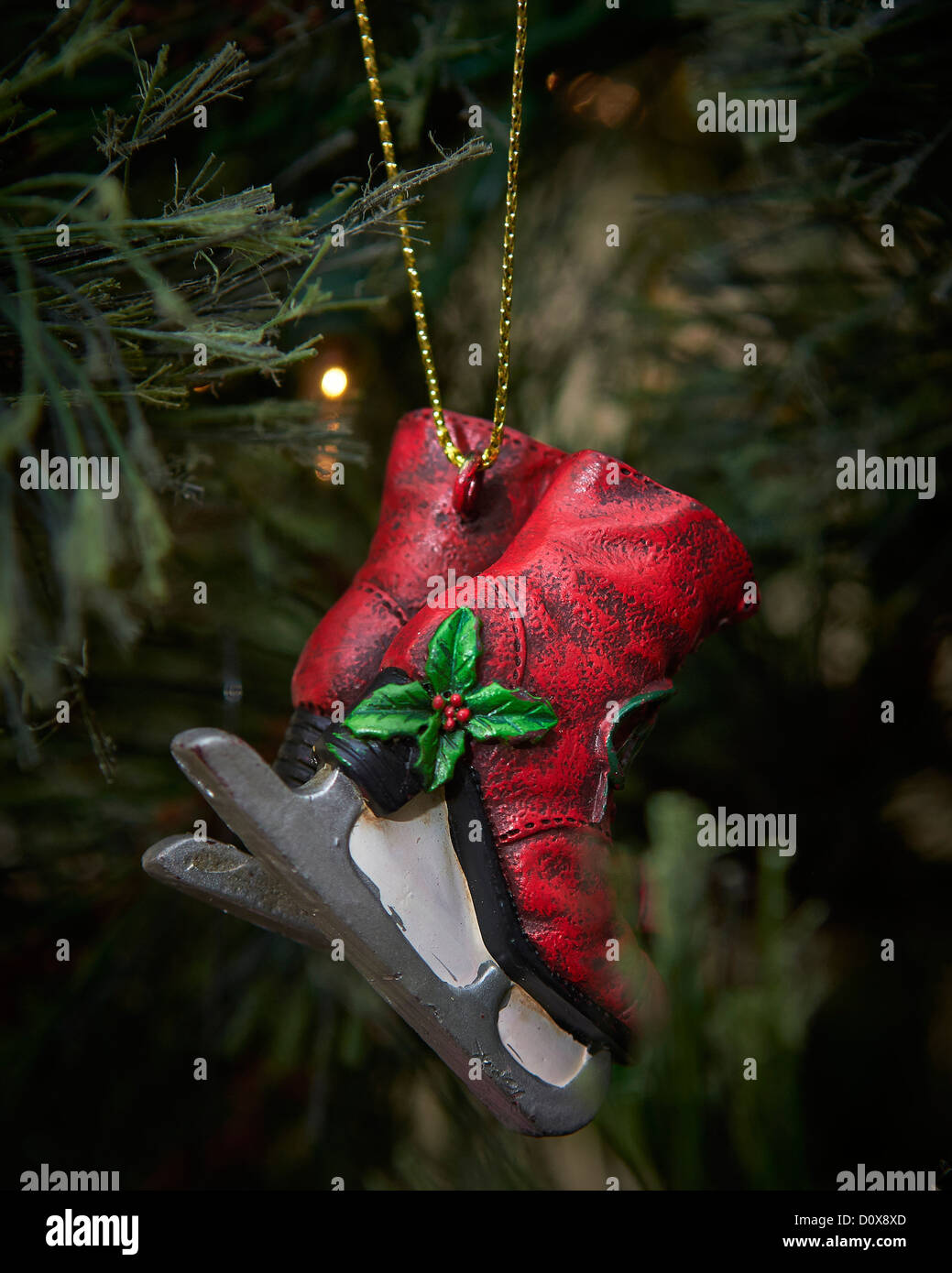 a christmas tree ornament of a pair of red ice skates and mistletoe hanging in