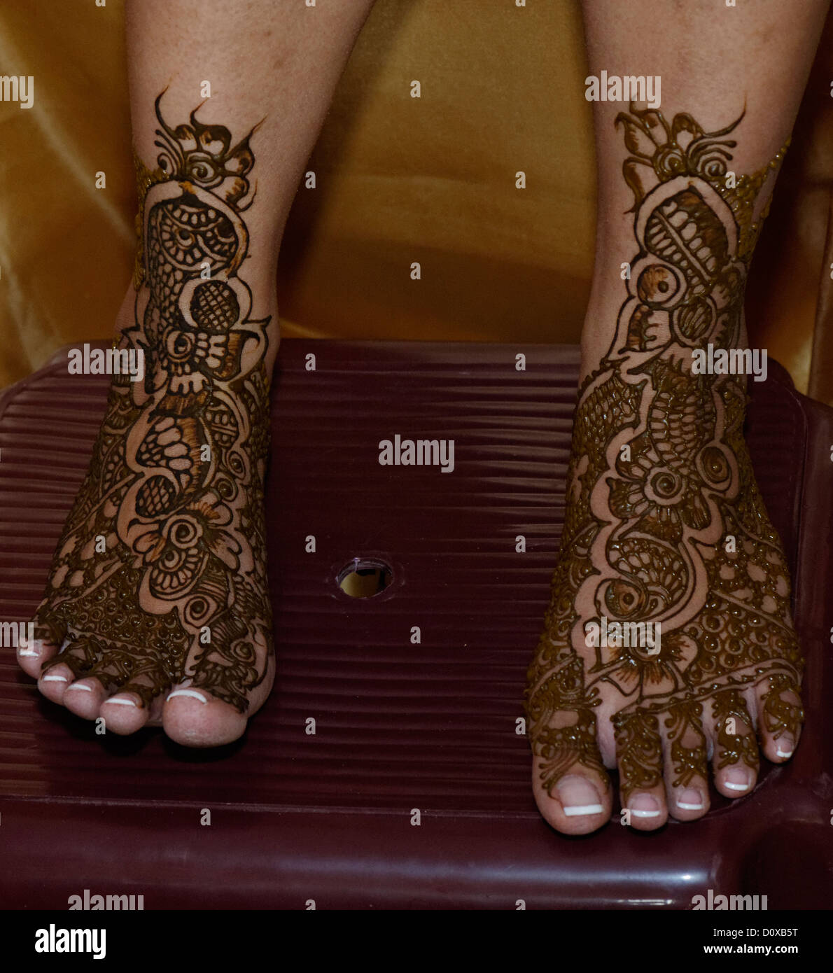 Traditional henna patterns painted on the feet of an bride
