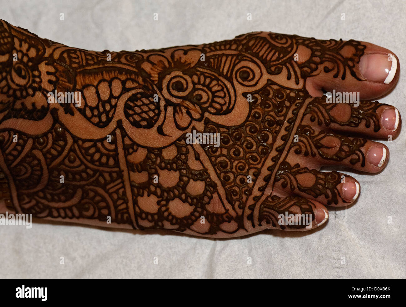 Traditional henna patterns painted on the foot of an bride