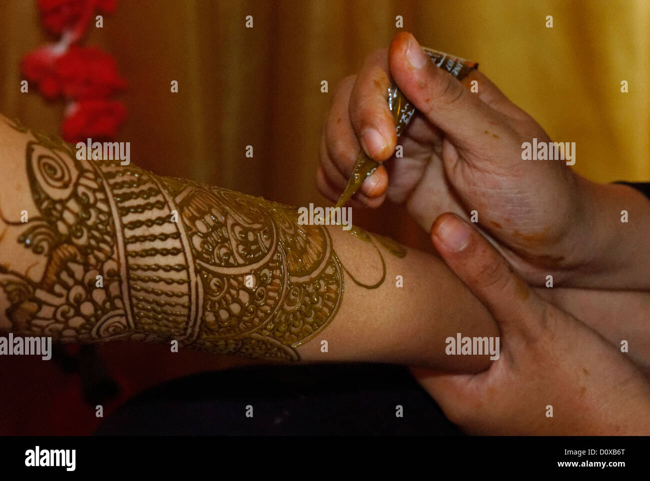 Hand Painting Traditional Designs In Henna On A Brides Arm For An