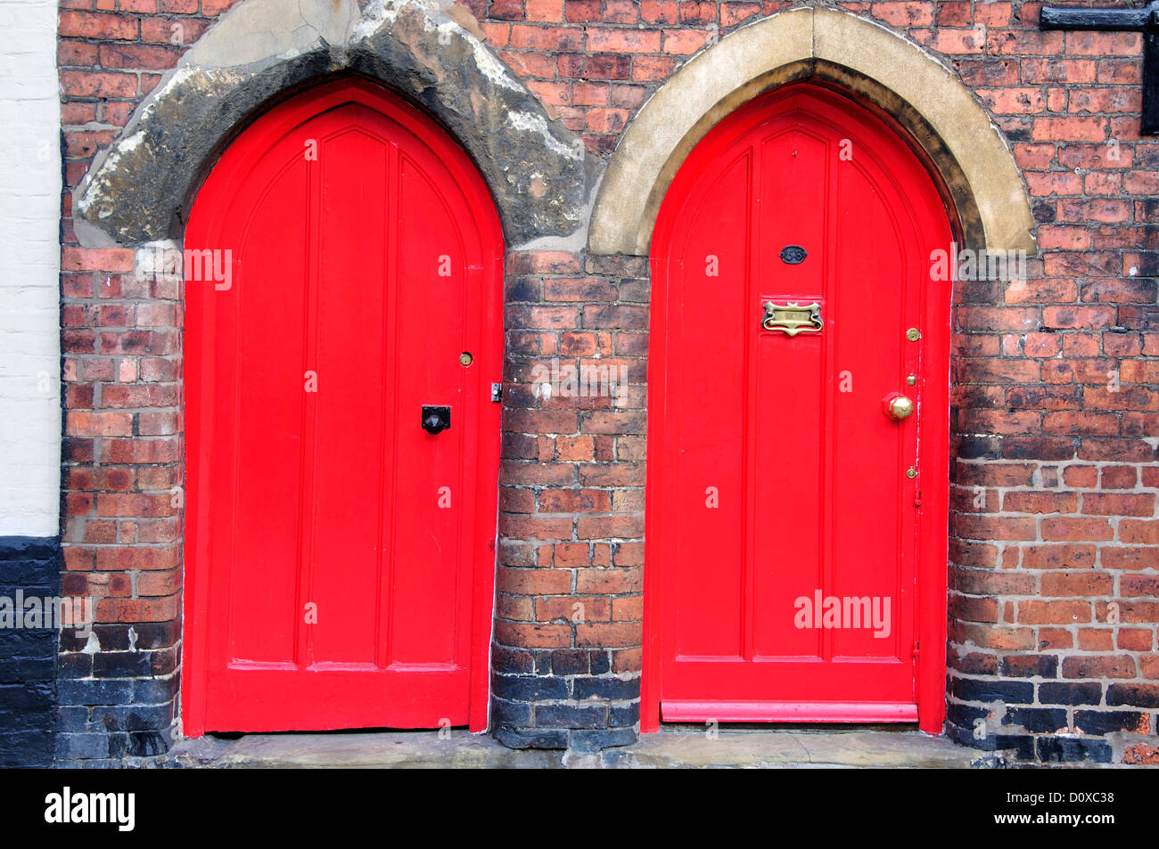 Two red arched doors UK - Stock Image