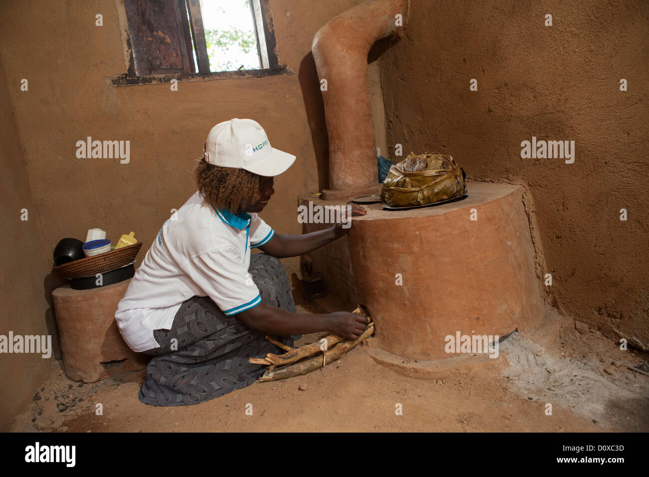 A woman uses an energy-saving stove in her kitchen on Bussi Island, Uganda, East Africa - Stock Image