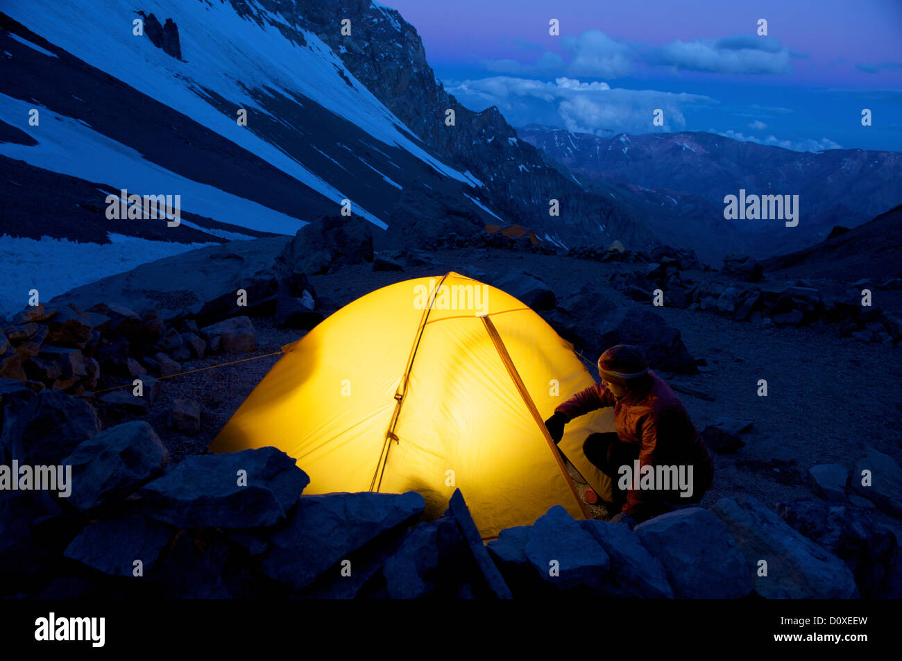 Woman unzips her tent at Camp One on Aconcagua in the Andes Mountains, Mendoza Province, Argentina - Stock Image