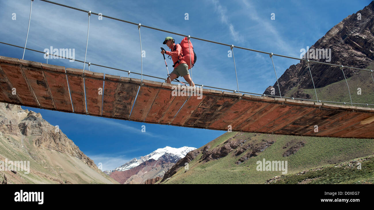 Woman crosses bridge over the Horcones River,  Aconcagua in the Andes Mountains, Mendoza Province, Argentina - Stock Image