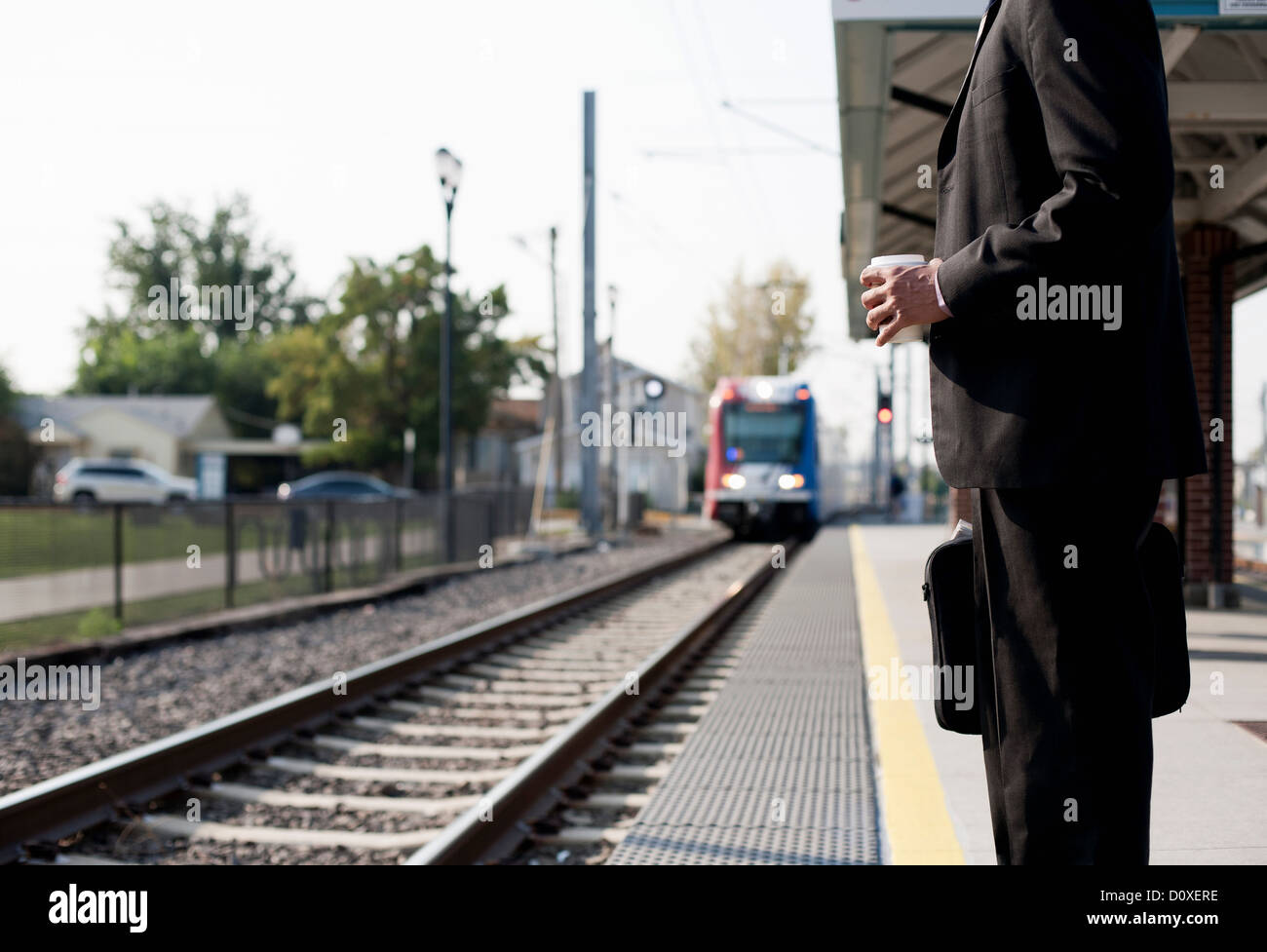 Businessman waiting for approaching train - Stock Image