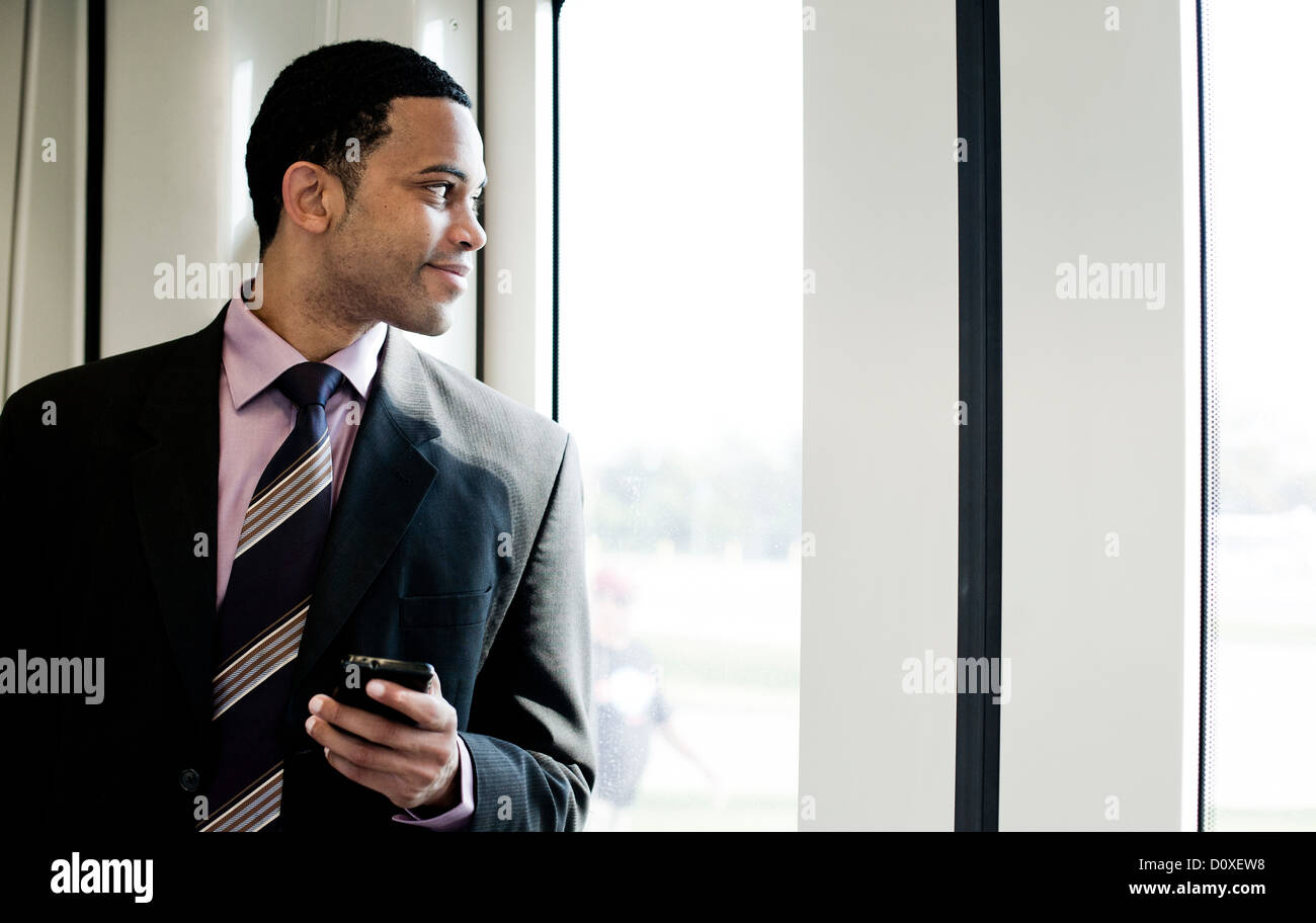 Businessman looking through window on a train - Stock Image