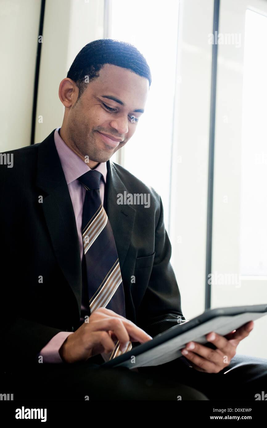 Businessman using digital tablet on a train - Stock Image