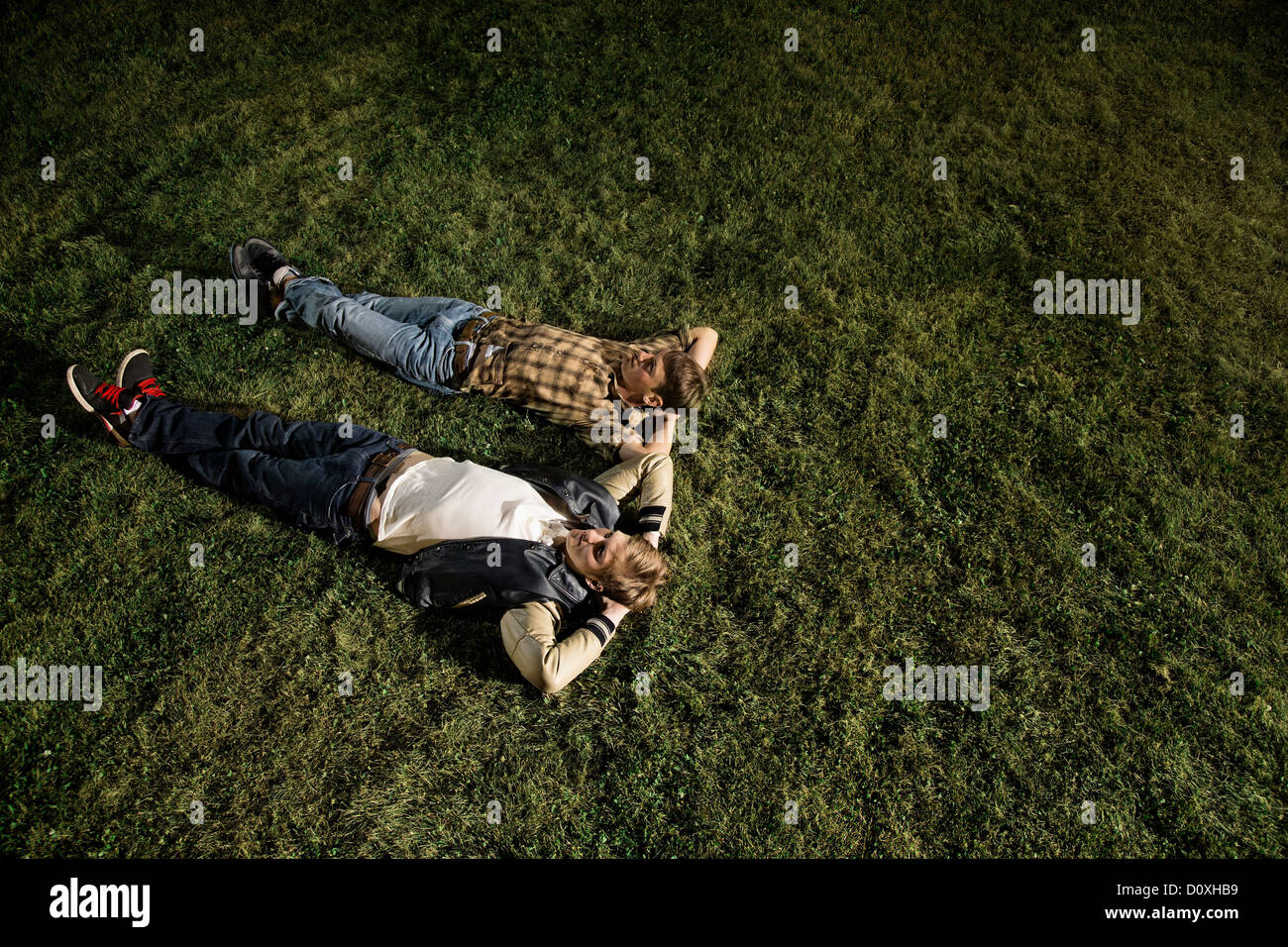 Two young men lying on grass at night, high angle - Stock Image