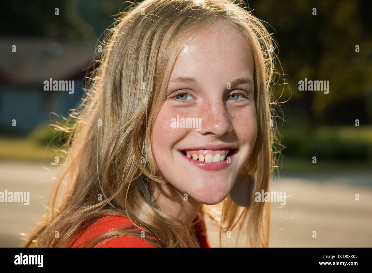 Close up portrait of blonde girl looking at camera smiling - Stock Image