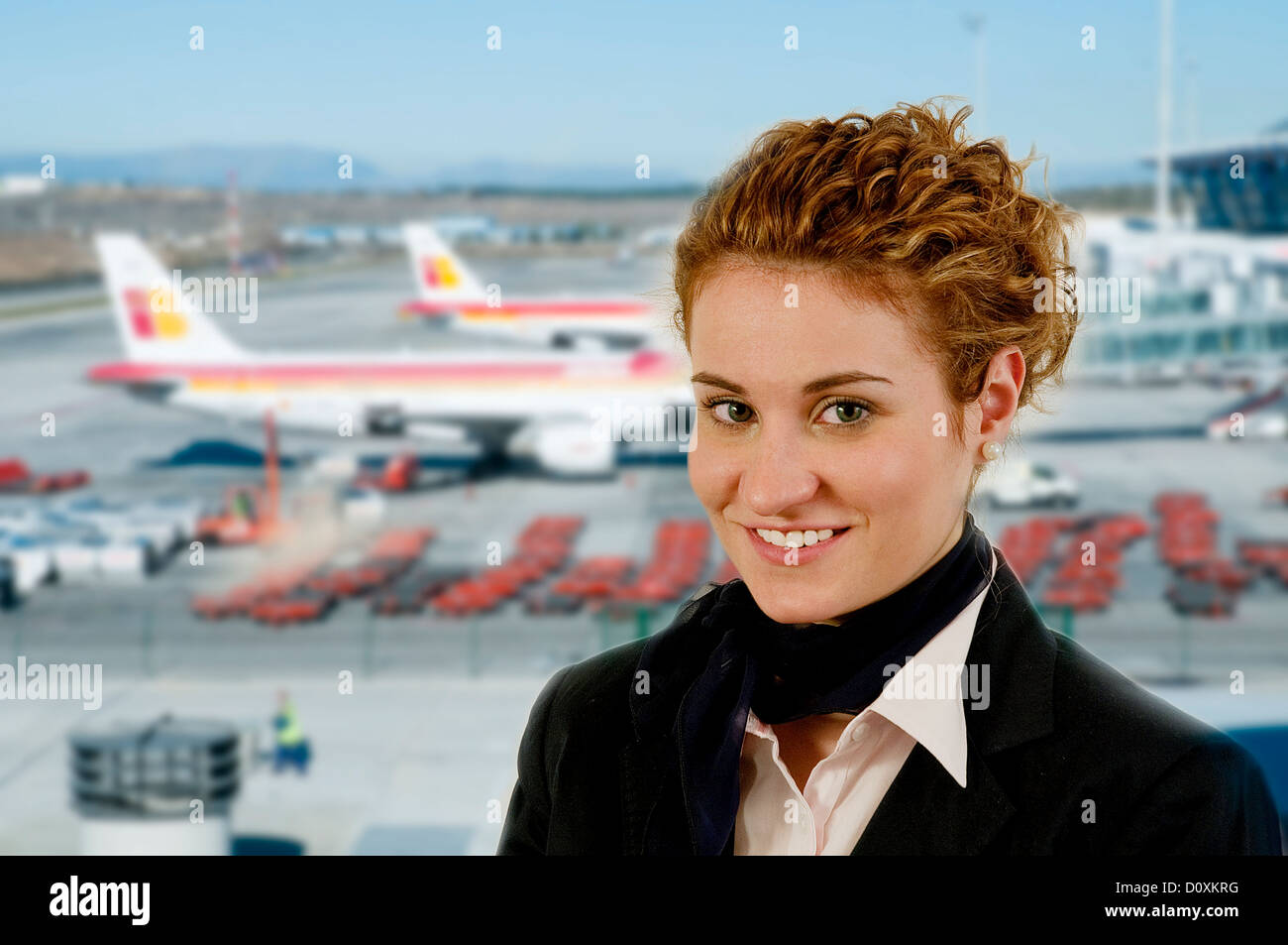 Young air hostess smiling and looking at the camera. - Stock Image