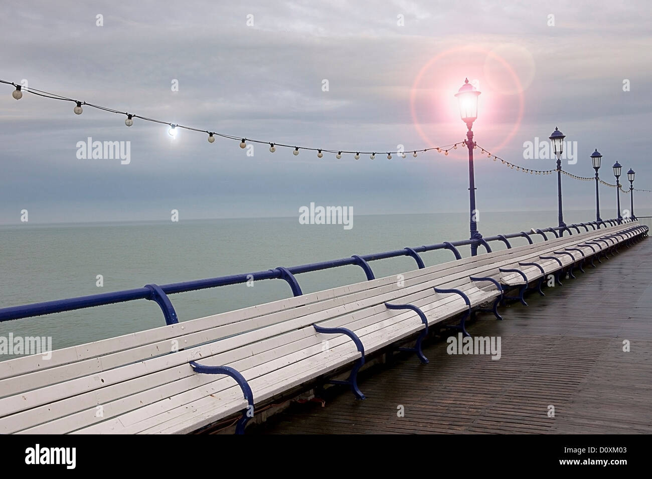 Empty benches on seaside pier, Eastbourne, East Sussex, UK Stock Photo