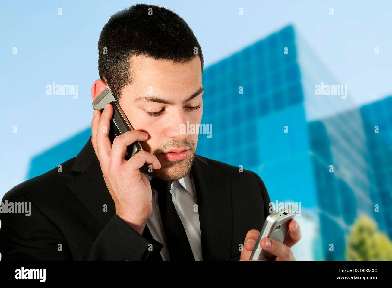 Young executive using two mobile phones. - Stock Image