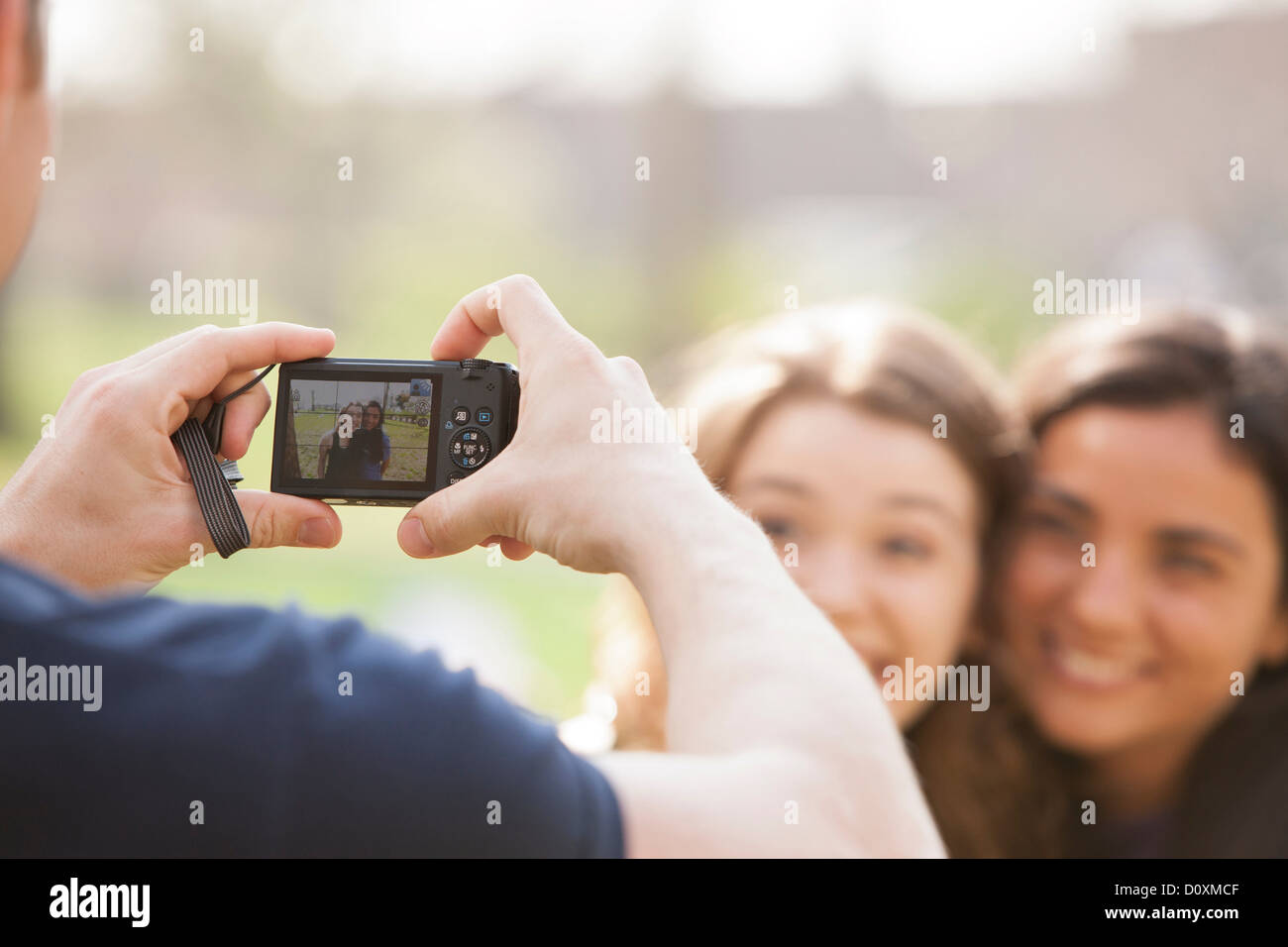 Man taking a photograph of two young women - Stock Image