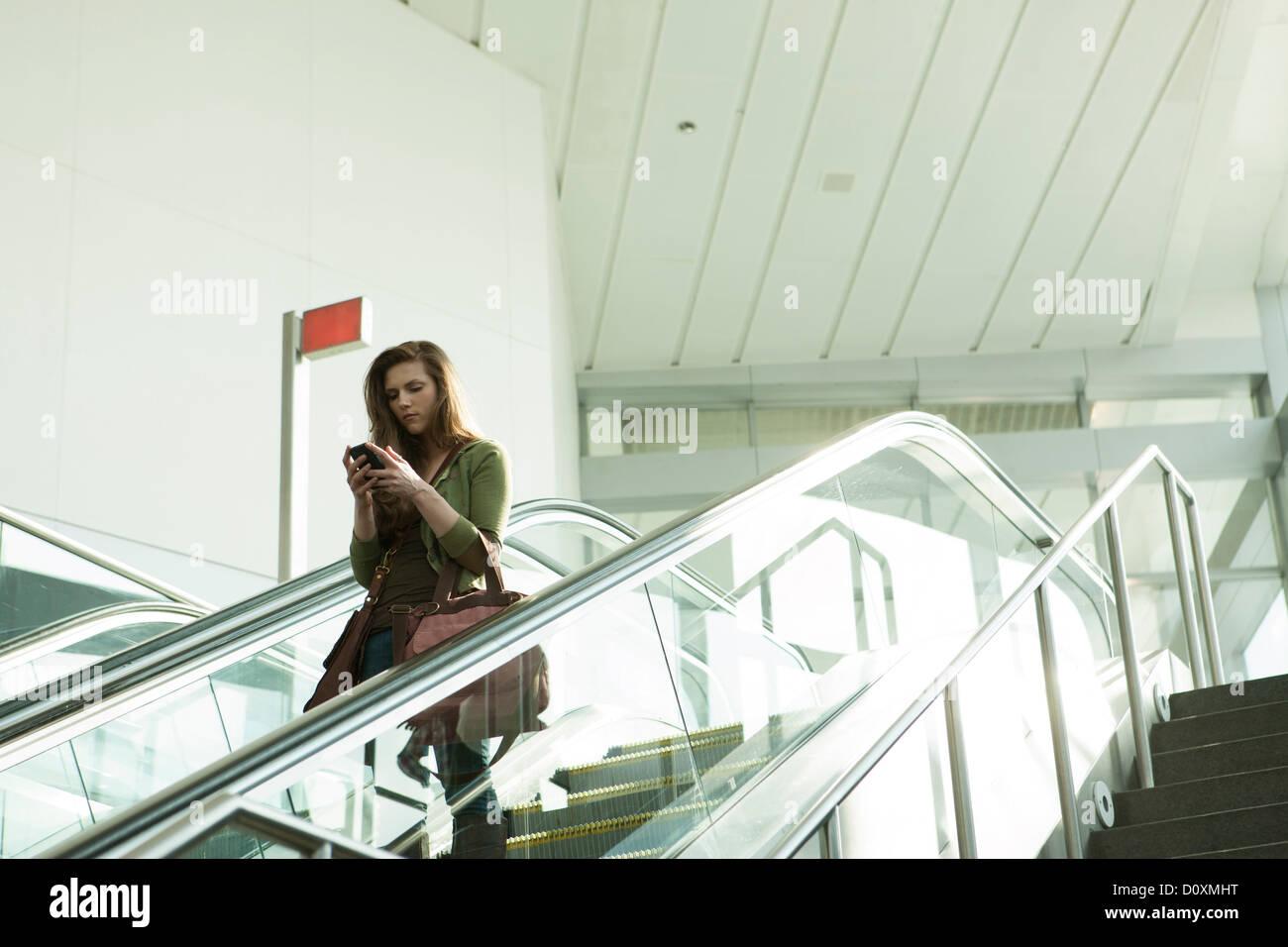 Young woman on escalator using smartphone - Stock Image