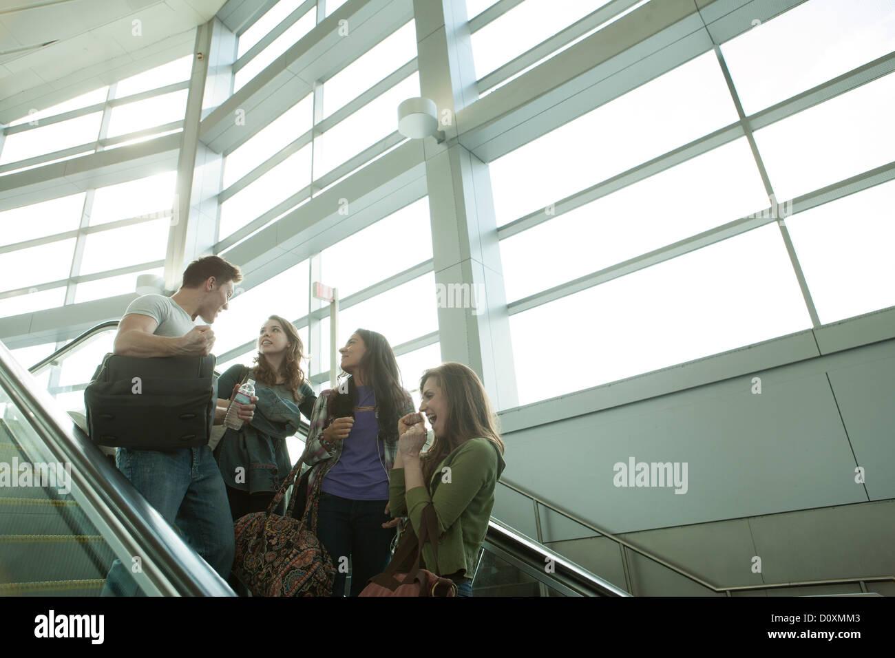 Friends travelling on escalator - Stock Image