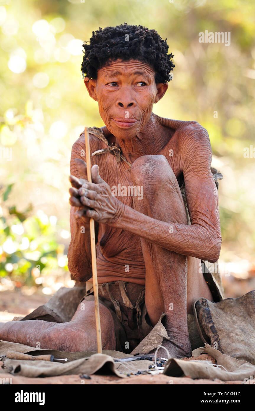 Africa Bushmen Namibia Portrait clan elder hunter gatherer natural nomad old older primitive sitting tools tribe - Stock Image